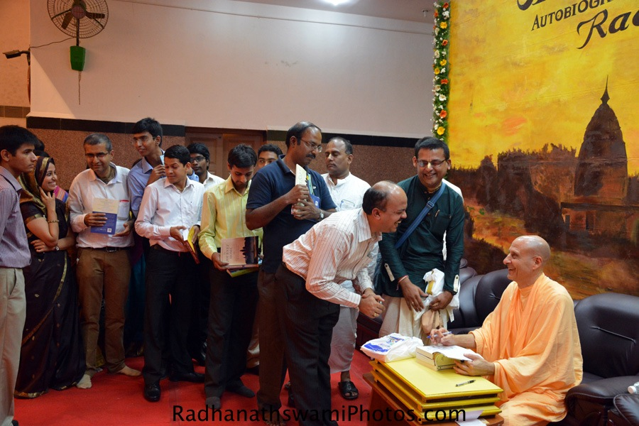 Radhanath Swami signing the book during chennai book launch