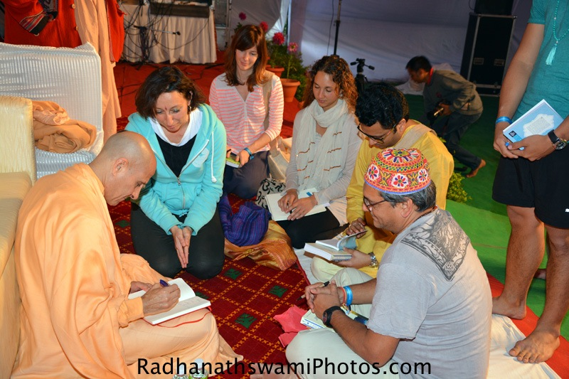 Radhanath Swami signs his book for yoga students at Rishikesh