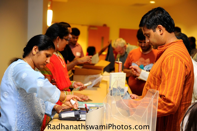 Guests buying a book of Radhanath Swami at center for spiritual center