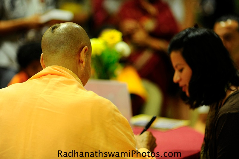 Radhanath Swami signing his book the journey home at center for spiritual living, seattle