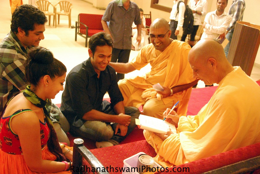 Radhanath Swami signing-his book