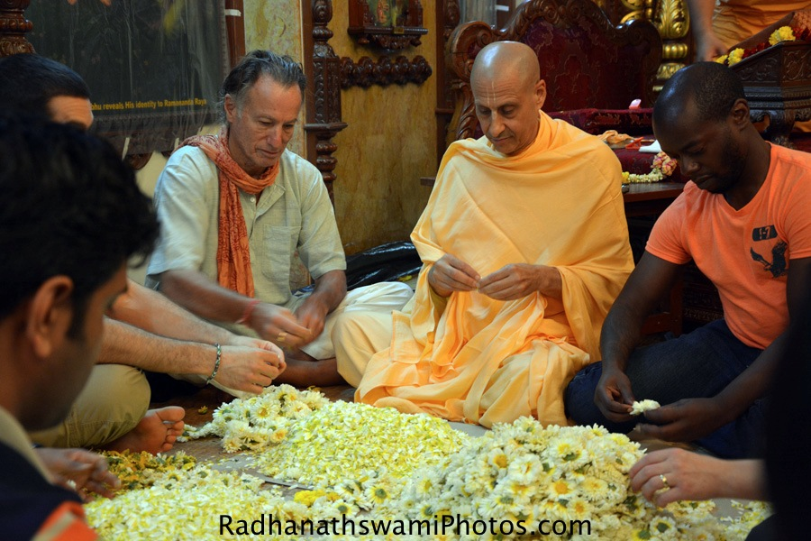 Radhanath Swami plucking flowers for lord
