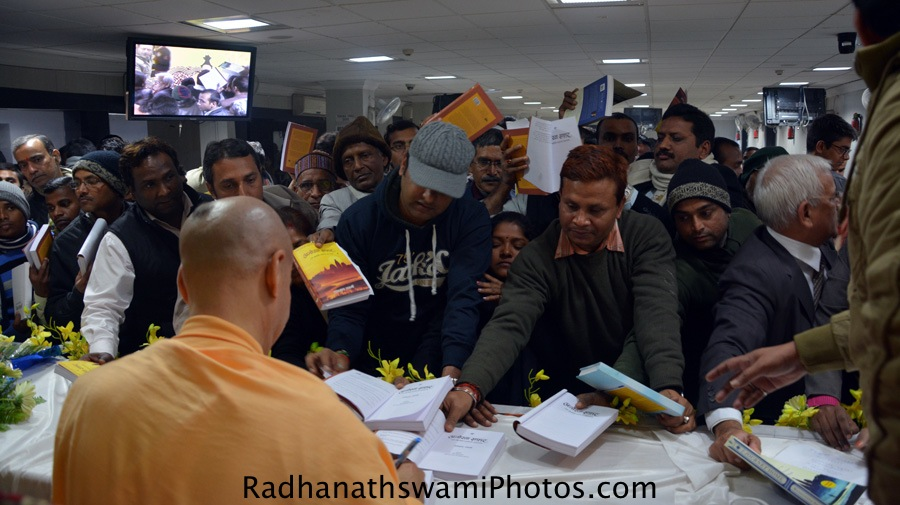 Radhanath Swami signing his book the journey home in Hindi