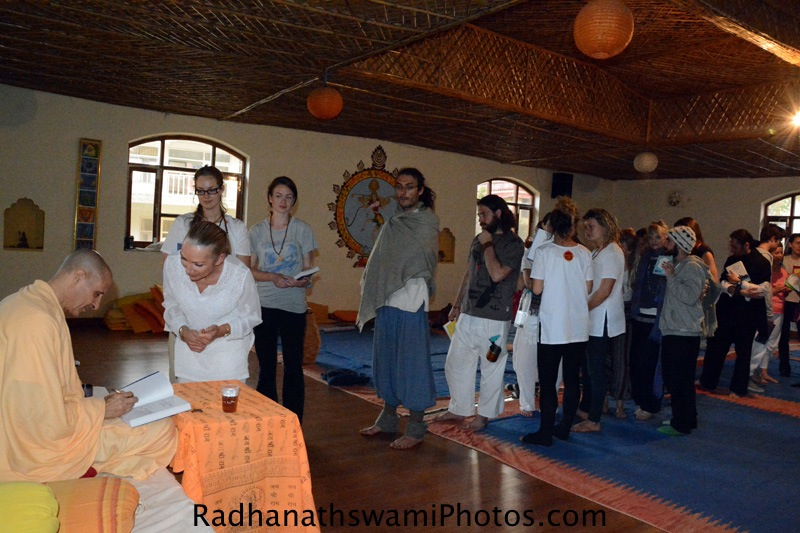 Radhanath Swami signing his book for the Yoga student
