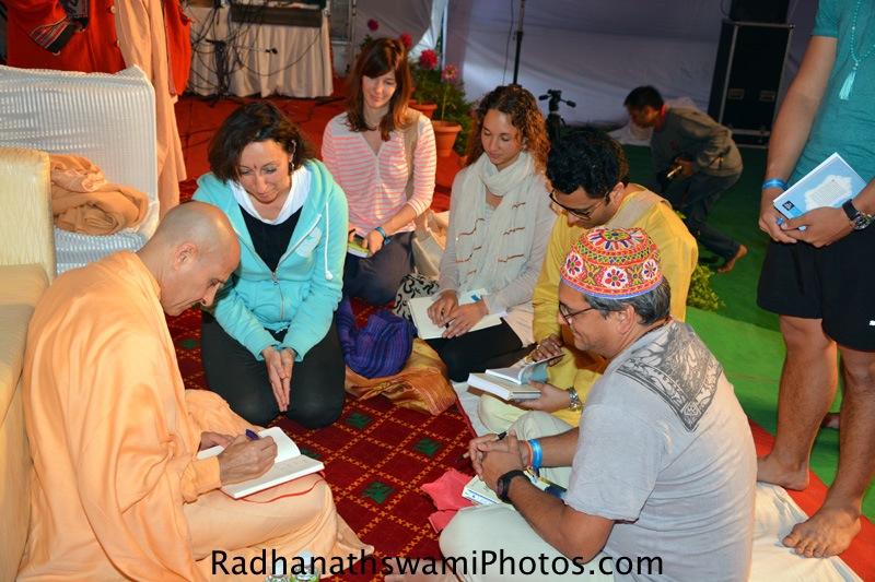 Radhanath Swami signs his book for yoga students at Rishikesh